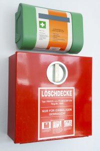 Brandschutzdecke zum Ersticken des Feuers im roten Aufbewahrungskasten an der Wand besfestigt, darüber Verbandskasten.