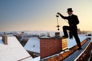 Schornsteinfegerarbeiten mit dem Kehrgerät auf dem Dach