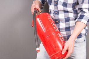 Ein Mann zeigt einen Feuerlöscher, für das richtige Verhalten im Brandfall