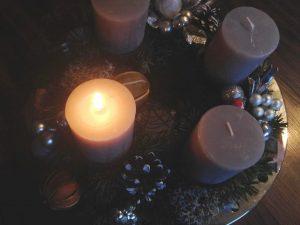 Adventskranz mit einer normal brennenden Kerze; Brandschutz in der Adventszeit